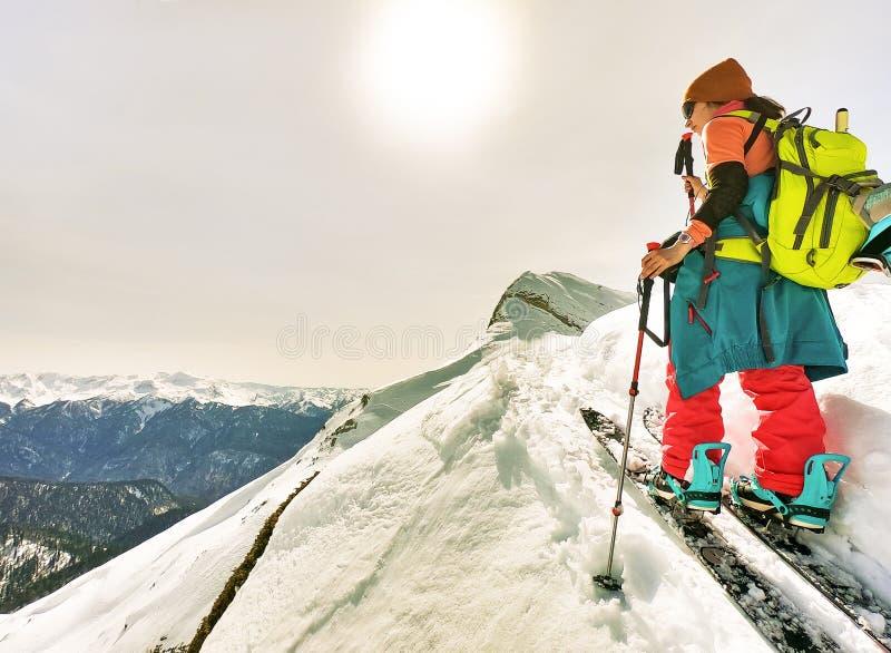 Den unga aktiva kvinnan med trekking poler skidar på turnerar arkivbild