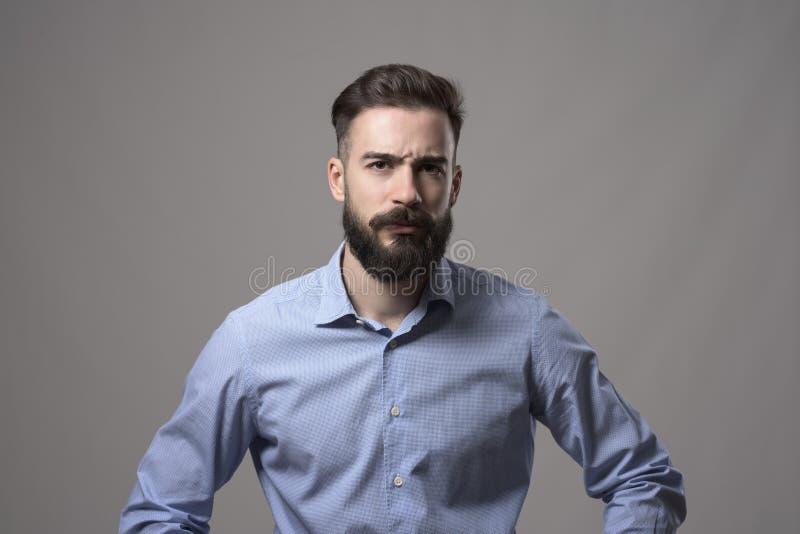 Den unga allvarliga rubbningen uppsökte affärsmannen med armar på höfter och intensiv blick på kameran royaltyfri foto