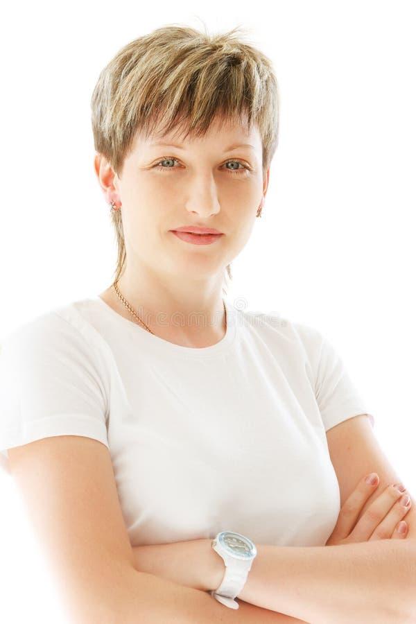 Den unga angenäma kvinnan på en vit bakgrund ler arkivbild