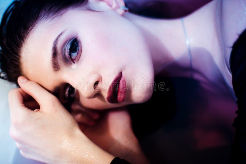 Den unga angenäma seende kvinnliga modellen tycker om det varma badet, visar hennes nakna skuldror Skönhet- och omsorgbegrepp royaltyfria foton