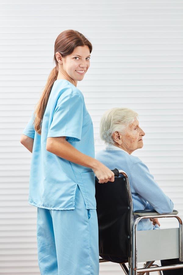 Den unga anhörigvårdaren skjuter den höga kvinnan i rullstol royaltyfri fotografi