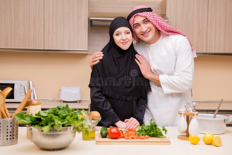 Den unga arabiska familjen i köket fotografering för bildbyråer
