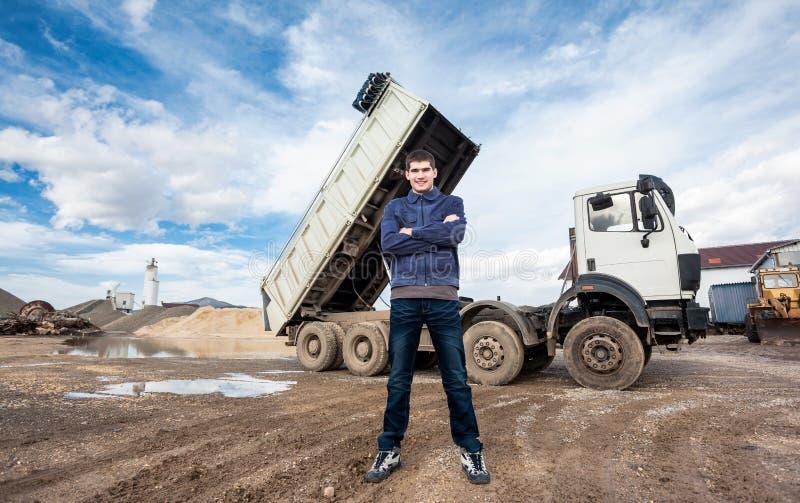 Den unga arbetaren och stora åker lastbil royaltyfri fotografi
