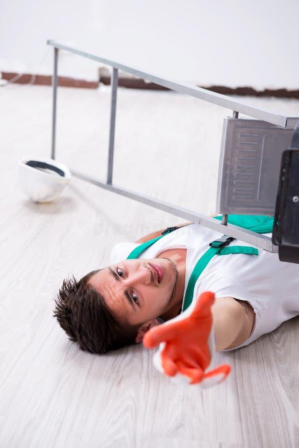 Den unga arbetaren som faller från stegen royaltyfria bilder