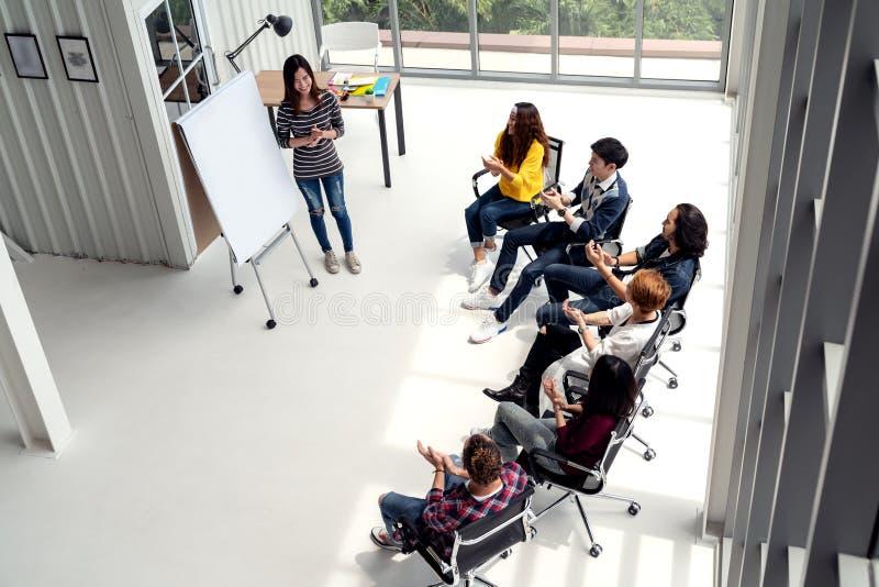 Den unga asiatiska affärskvinnan förklarar idé till gruppen av det idérika olika laget på det moderna kontoret fotografering för bildbyråer