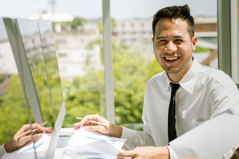 Den unga asiatiska affärsmannen ler lyckligt på ett skrivbord mycket av docume royaltyfria foton