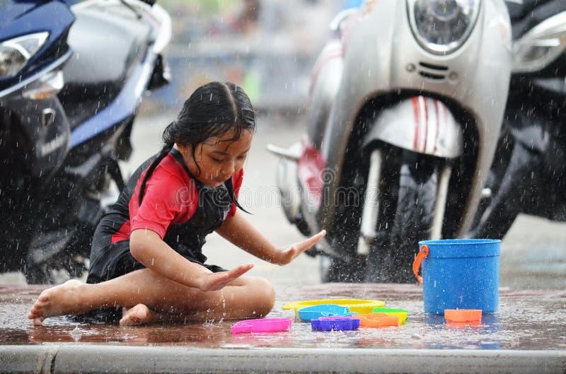 Den unga asiatiska flickan älskar att spela i regnet under monsunsäsong i Thailand royaltyfri bild