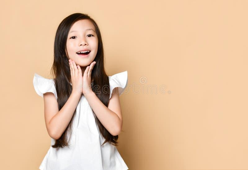 Den unga asiatiska flickan förvånade upphetsat lyckligt skrika Gladlynt unge med roligt glat framsidauttryck royaltyfri fotografi
