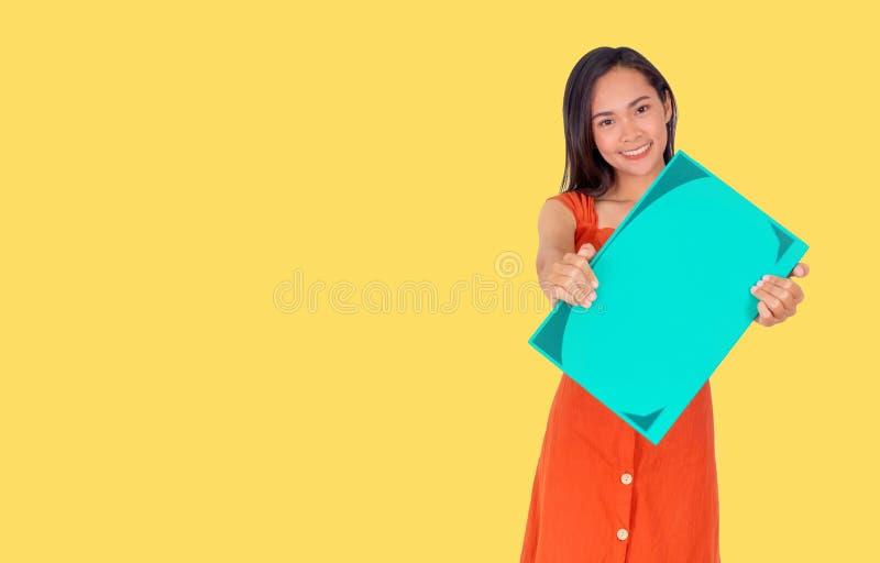 Den unga asiatiska flickan i orange klänning visar en stor grön bok till den gula bakgrunden för kameran royaltyfri fotografi