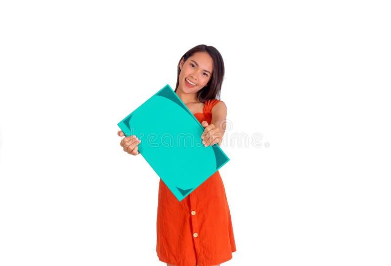 Den unga asiatiska flickan i orange klänning visar en stor grön bok till den vita bakgrunden för kameran royaltyfria bilder