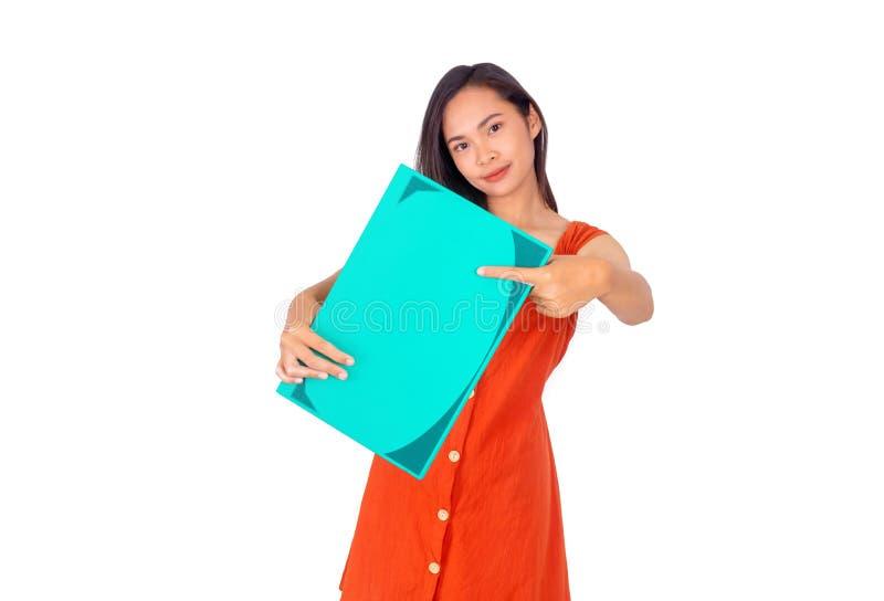 Den unga asiatiska flickan i orange klänning visar en stor grön bok till den vita bakgrunden för kameran royaltyfria foton