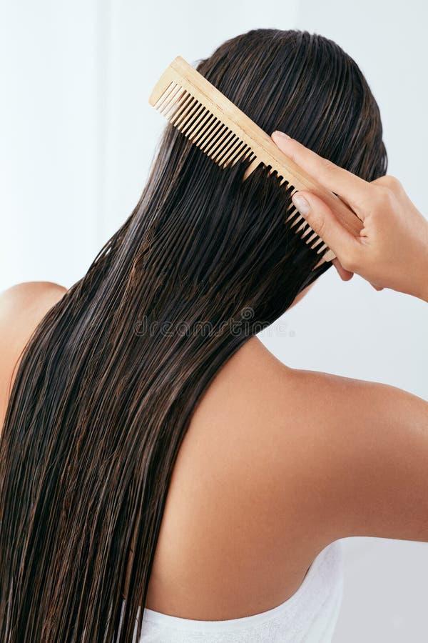 Den unga asiatiska flickan som kammar hår med, fingrar isolerat på vitbakgrund Härlig kvinna som borstar vått långt hår efter bad royaltyfria foton
