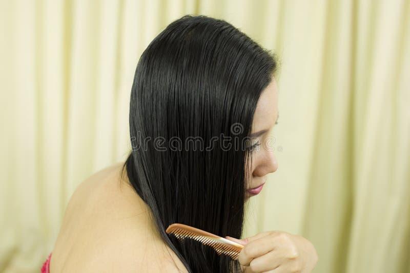 Den unga asiatiska flickan som kammar h?r med, fingrar isolerat p? vitbakgrund Closeup av h?rligt kvinnaHairbrushing h?r med bors arkivfoto