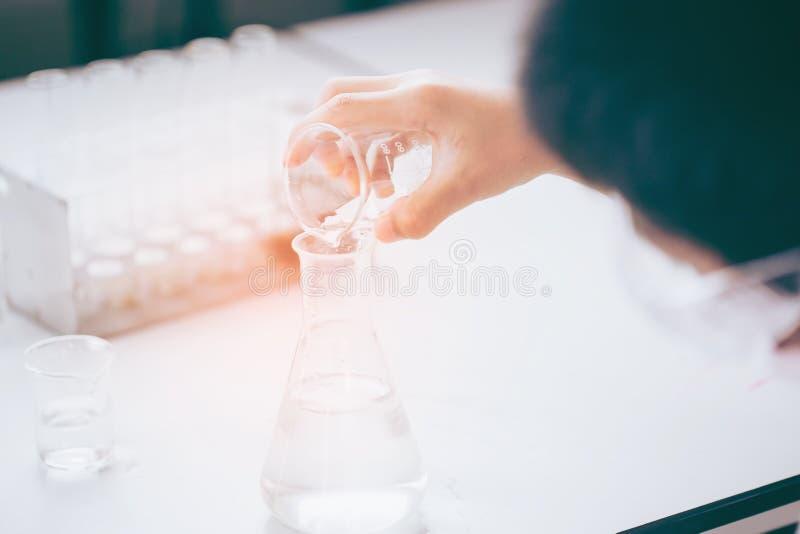 Den unga asiatiska forskaren är bestämda aktiviteter på experimentell vetenskap som blandande kemikalieer eller tillträdesdata so arkivfoto
