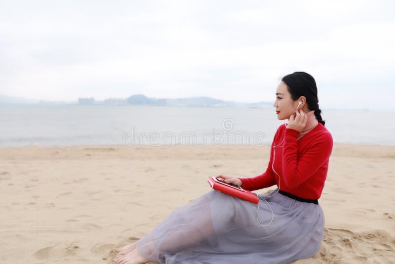 Den unga asiatiska kinesiska kvinnan läste sitter på hennes sida i sandläseboken på stranden royaltyfria foton