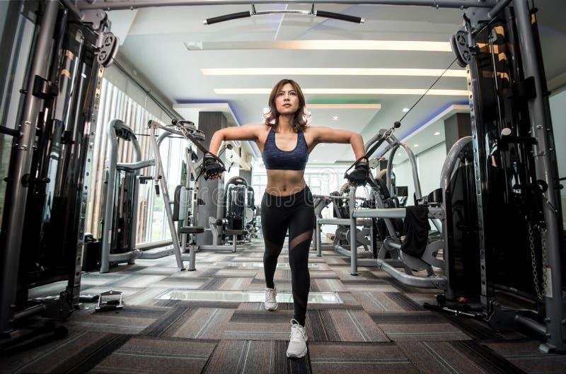 Den unga asiatiska konditionkvinnan utför övning med övning-maskinen royaltyfri bild