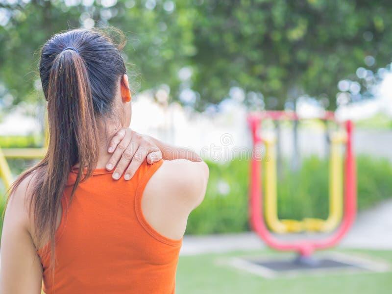 Den unga asiatiska kvinnakänseln smärtar på hennes hals och skuldra arkivbild