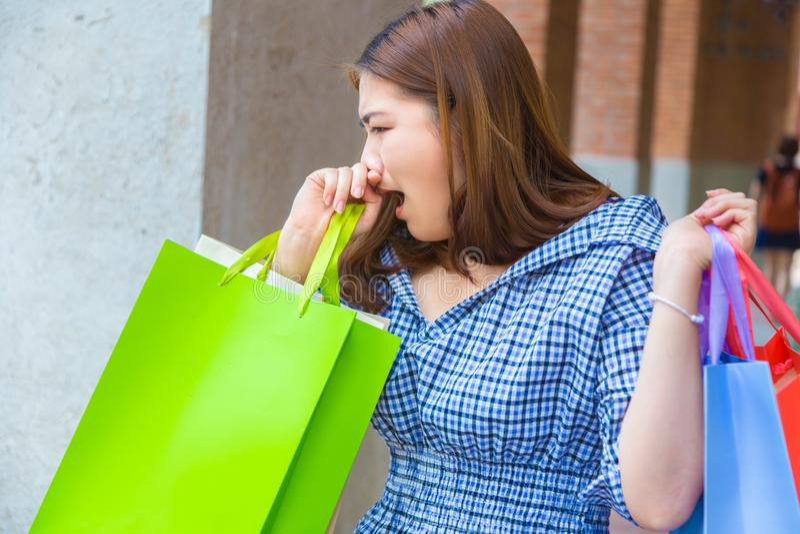 Den unga asiatiska kvinnan är trött och gäspa från lång dag av shopping fotografering för bildbyråer