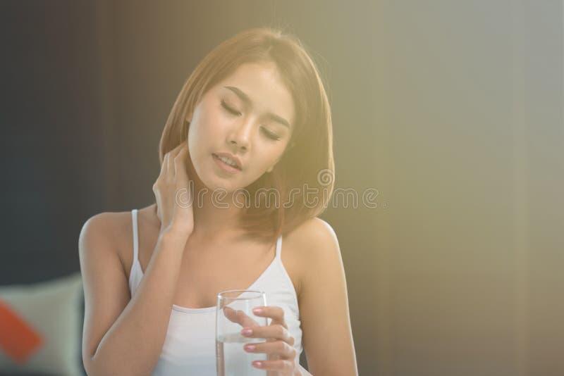 Den unga asiatiska kvinnan har en smärta i halsen arkivbilder