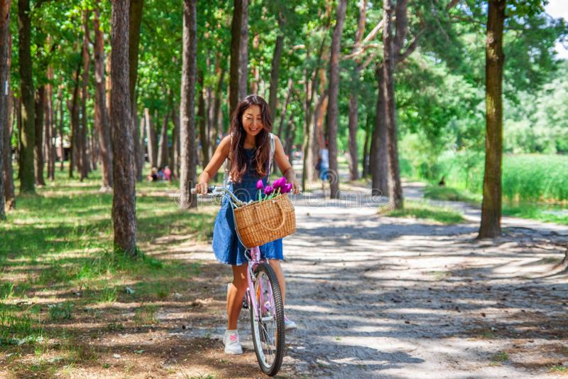 Den unga asiatiska kvinnan i klänning med långt hår rider en cykel med korgen, och blommor turnerar sommarstaden parkerar, ser oc royaltyfri bild