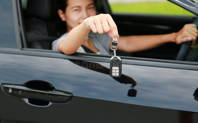 Den unga asiatiska kvinnan inom en bil, rymmer tangenten ut fr?n f?nstret Fokus på nyckel- hänga på hennes hand arkivfoton
