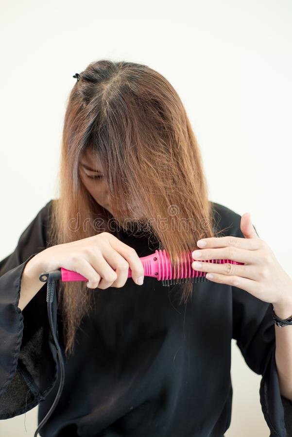 Den unga asiatiska kvinnan rymmer hårstraighteners royaltyfri bild