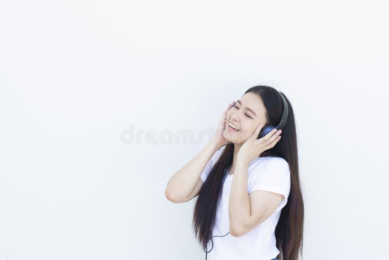 Den unga asiatiska kvinnan ska tycka om livsstil, genom att lyssna till musik royaltyfri foto