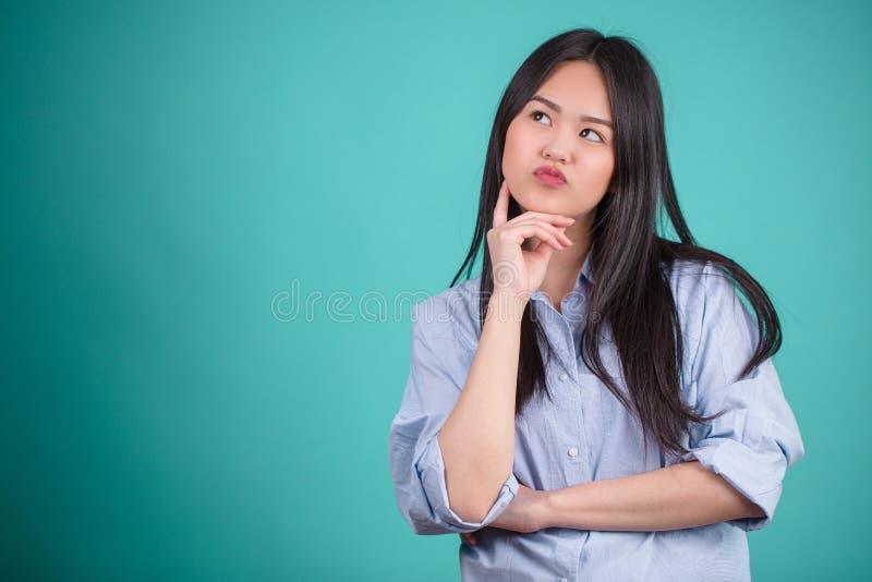 Den unga asiatiska kvinnan som gör en gest i defferent, poserar över blå backgro arkivbilder