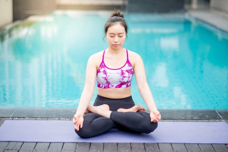 Den unga asiatiska kvinnan som gör yogaövning med lotusblommaposition, poserar royaltyfri foto