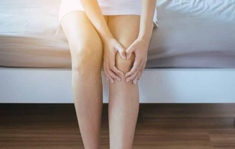 Den unga asiatiska kvinnan som har ett knä, smärtar, smärtsam kvinnlig känsla som evakueras och royaltyfri bild