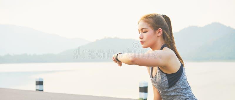 Den unga asiatiska kvinnan som ser sportarna, håller ögonen på och kontrollerar hennes kapacitet P? v?gen royaltyfri fotografi