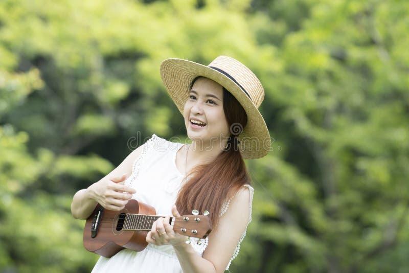 Den unga asiatiska kvinnan spelar gitarren och sjunger en sång royaltyfria bilder