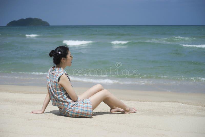 Den unga asiatiska kvinnan tar en vila på stranden med suddig havsbakgrund, den selektiva fokusen, naturlig färgbildstil royaltyfri bild