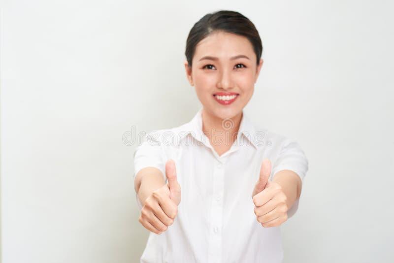 Den unga asiatiska kvinnan visar tummen övre gest genom att använda båda händer arkivbild