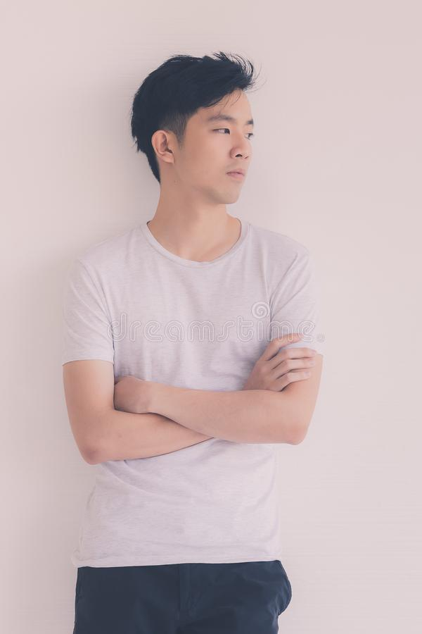 Den unga asiatiska manmodellen i T-tr?ja korsade armen fotografering för bildbyråer