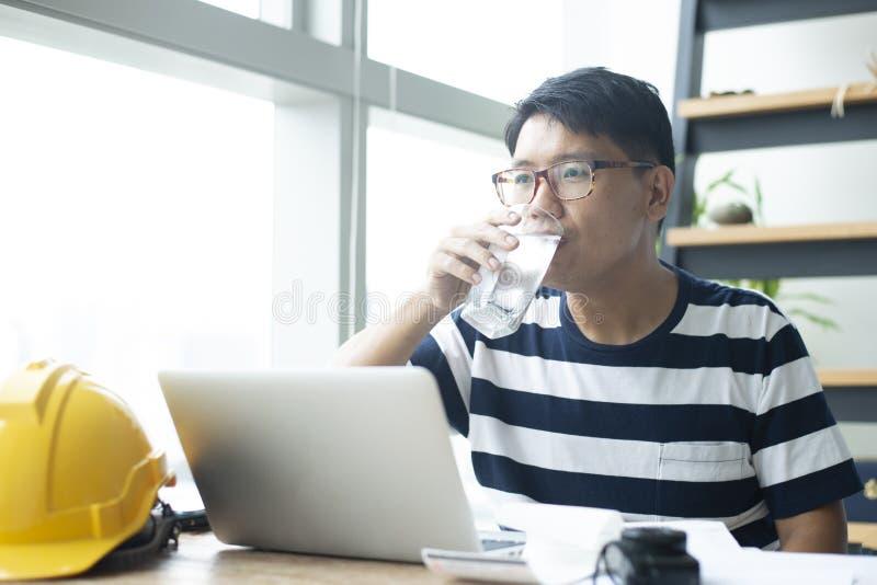 Den unga asiatiska mannen är dricksvatten, medan arbeta arkivbild