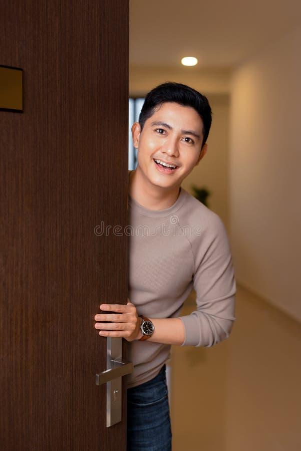 Den unga asiatiska mannen öppnar hans främre dörr och le för hus royaltyfri bild