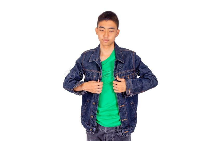 Den unga asiatiska mannen i grön t-skjorta sätter på jeansomslaget royaltyfri bild