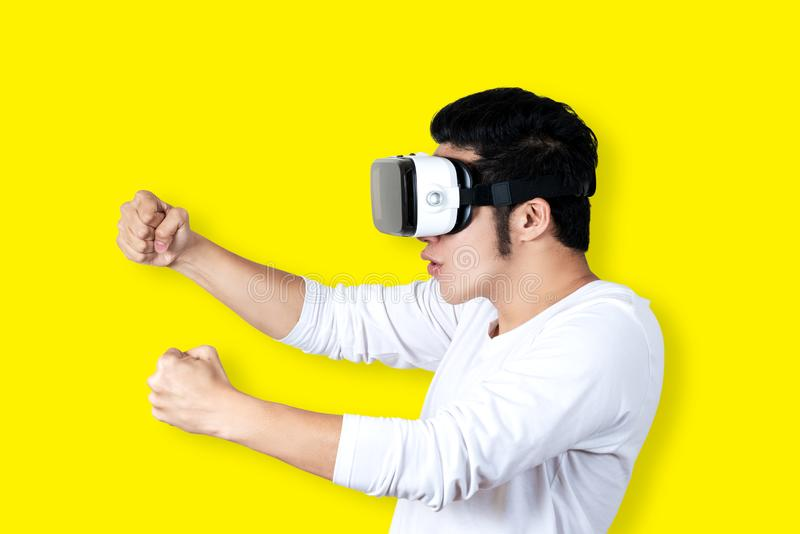 Den unga asiatiska mannen i den tillfälliga dräkten som rymmer eller bär VR-exponeringsglas, rullar med ögonen spela videospelet  royaltyfri foto