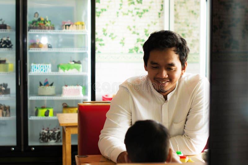 Den unga asiatiska mannen med hennes begynnande son p? kakalagret, den unga asiatiska mannen som spenderar tid med hans, behandla royaltyfri bild