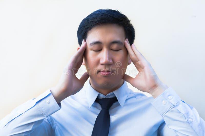 Den unga asiatiska mannen som har huvudvärk/spänning/, överansträngde i regeringsställning royaltyfri fotografi