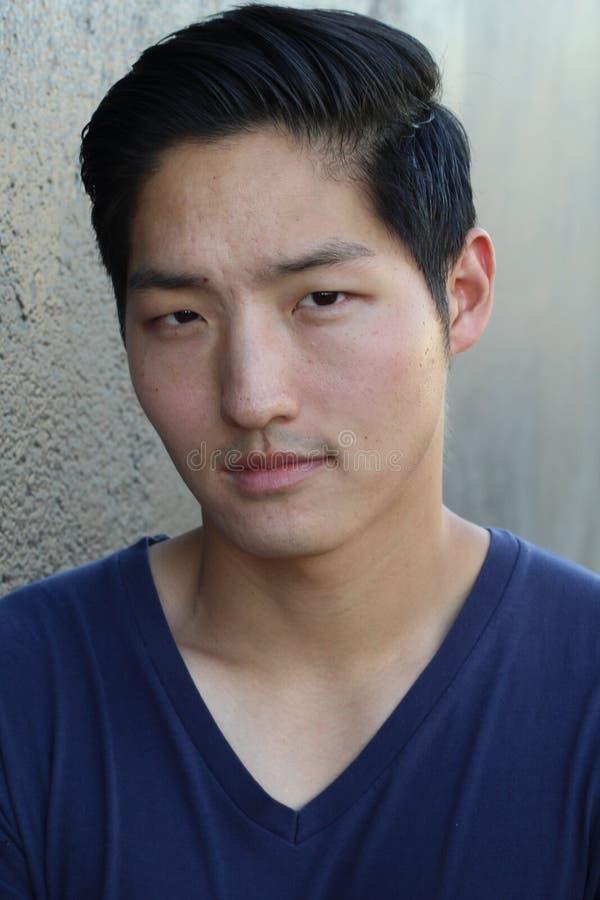Den unga asiatiska mannen som ser kameran - lagerföra bilden royaltyfri foto
