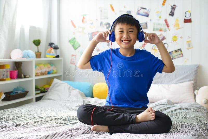Den unga asiatiska pojken är le och lyssna till musik royaltyfri bild