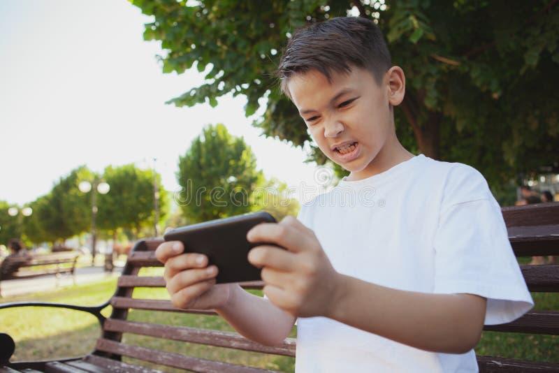 Den unga asiatiska pojken som spelar lekar på hans smarta telefon på, parkerar royaltyfri foto