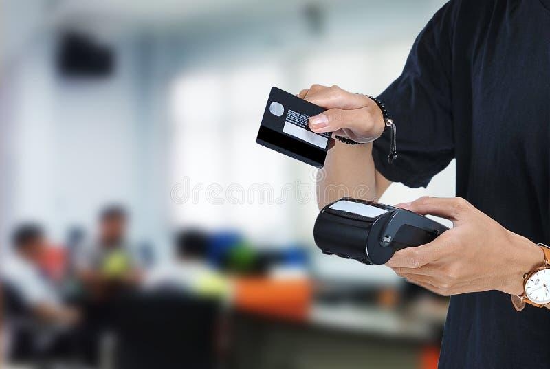 Den unga asiatiska studenten som rymmer elektroniska data fångar EDC-maskinen, och klara att nalla kreditkorten eller debiteringk arkivfoton