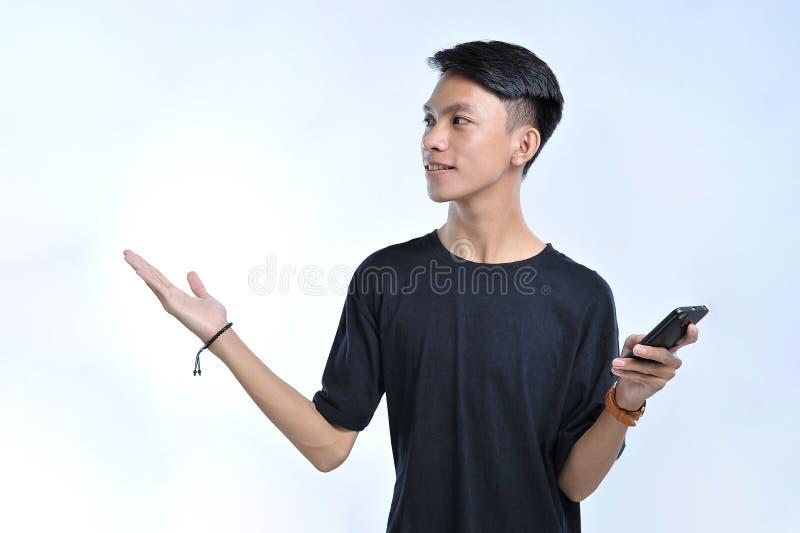 Den unga asiatiska studentmannen som rymmer en smart telefon, och den öppna handen gömma i handflatan åt sidan och att framlägga  arkivfoton
