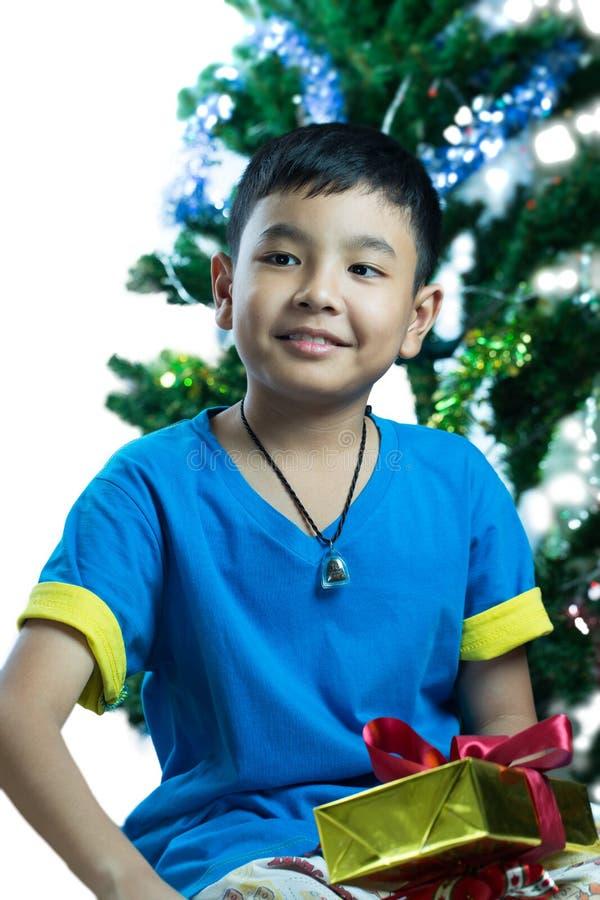 Den unga asiatiska ungen får hans julgåva arkivbild