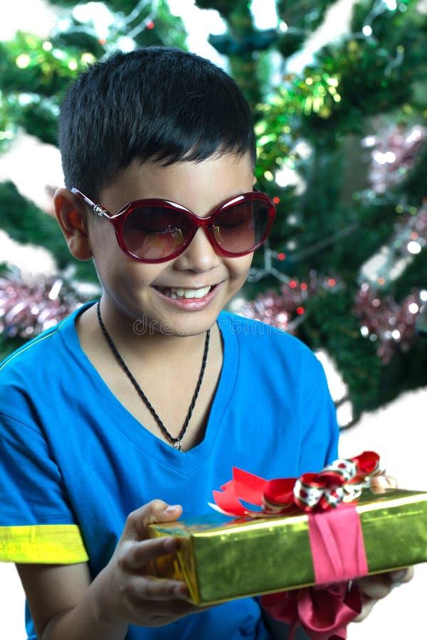 Den unga asiatiska ungen på sunglass ser hans julklapp royaltyfria foton