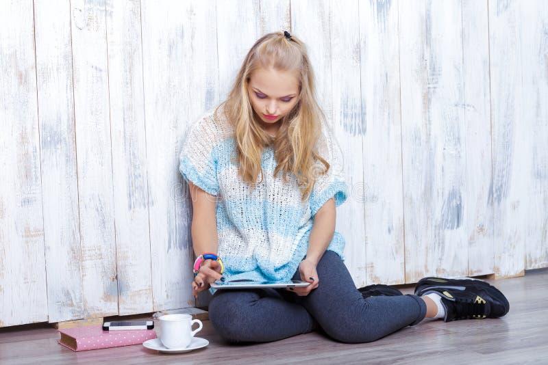 Den unga attraktiva blonda kvinnan använder minnestavlan framme av den vita träväggen royaltyfria foton