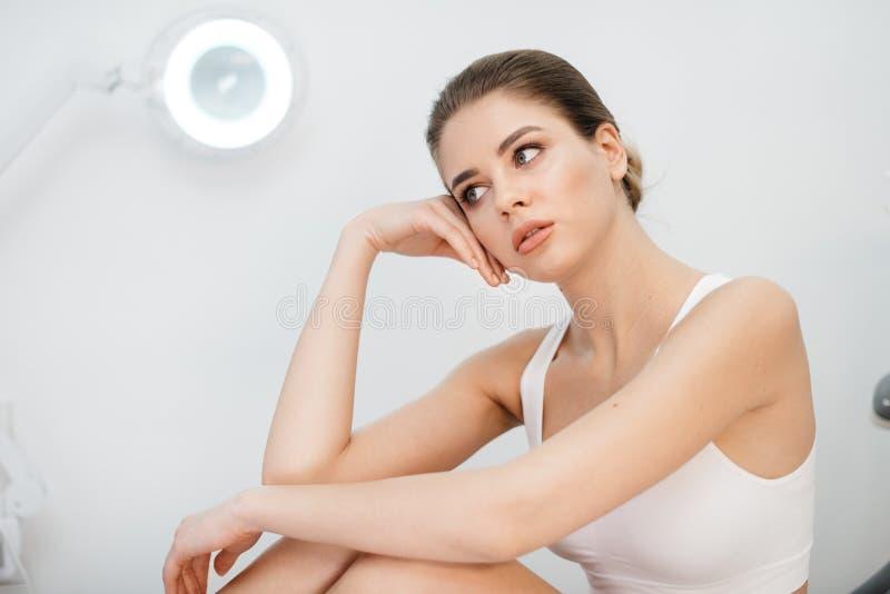 Den unga attraktiva blonda kvinnan med naturlig smink- och porslinhud poserar på den vita bakgrunden Hon lutar royaltyfria foton